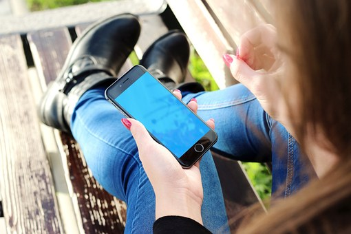 A woman laying on a bench and looking at her iPhone
