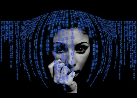 A woman's face behind some binary code moulding around her face
