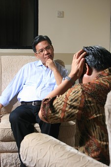 A male therapist talking to a male client in a therapy session