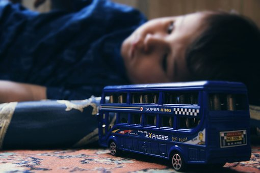 A sad child behind a small toy bus