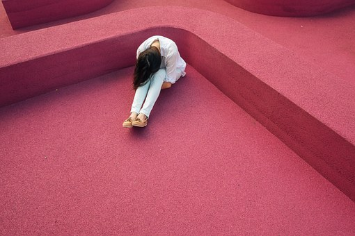 A lonely person in a crouched position separated from others by red walls