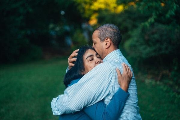 A man and a woman hugging each other near trees