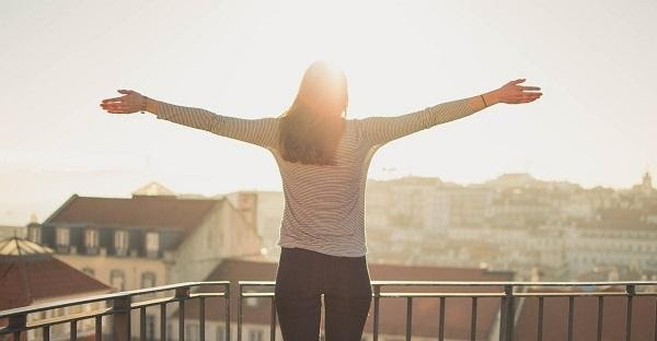 A woman with her arms extended out on a balcony and looking out over a sunrise