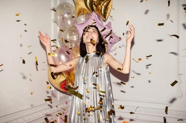 A woman with falling confetti and balloons at a Birthday party