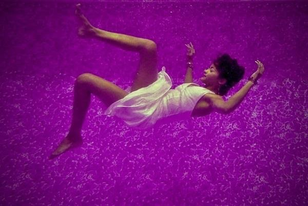 A woman floating in a purple liquid with a white dress on